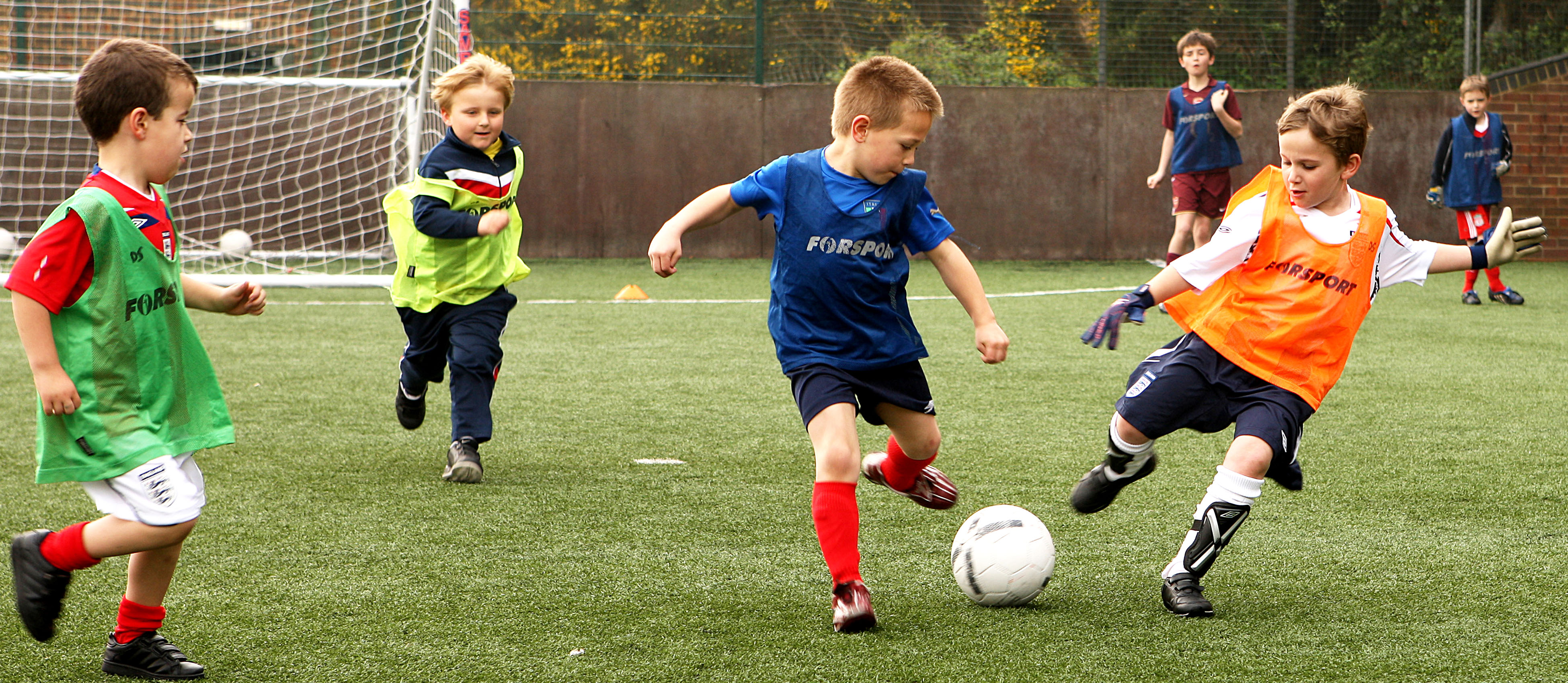 Kids aged 4-10 playing football at an SCL Saturday Soccer venue.